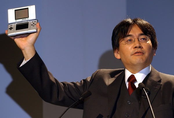 "Nintendo Co. President Satoru Iwata raises up the video game maker's new portable game player ""Nintendo DS"" as he launches the handheld player in Tokyo Thursday, Oct. 7, 2004. Nintendo hopes the gadget, featuring double screen, touch screen, wireless and microphone, helps strengthen its global share of gaming market. The player will go on sale on Nov. 21 in the United States and Dec. 2 in Japan. (AP Photo/Katsumi Kasahara)"