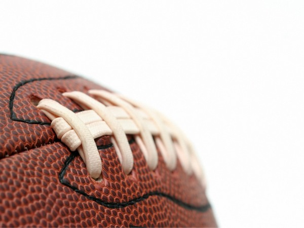 american football - macro with focus on first stitch, shot over white