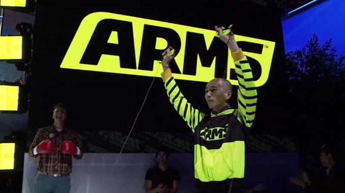 Das Foto zeigt ARMS-Director Kosuke Yabuki in voller Montur mit zwei Joy-Cons in den Händen.